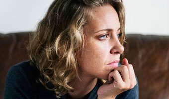 Woman, with hand on her chin, experiencing anxiety