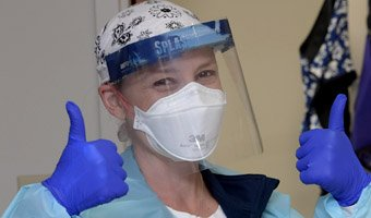 Close up photo of a Cottage Nurse wearing personal protective equipment giving two thumbs up