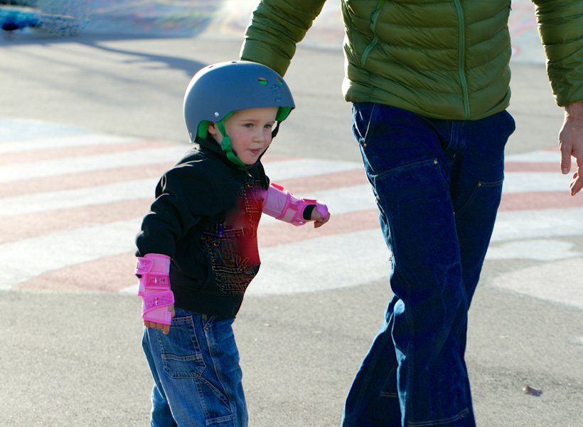 Dad holding young girl's hand while riding a skateboard