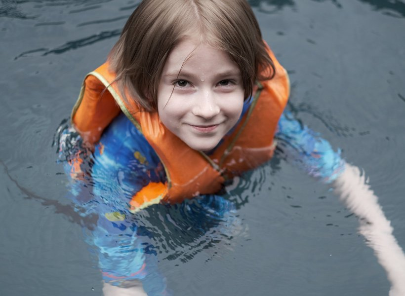 Child wearing a life jacket floating in the water