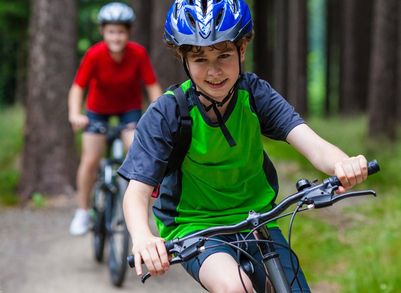 Child smiling and riding a bicycle with his helmet on.