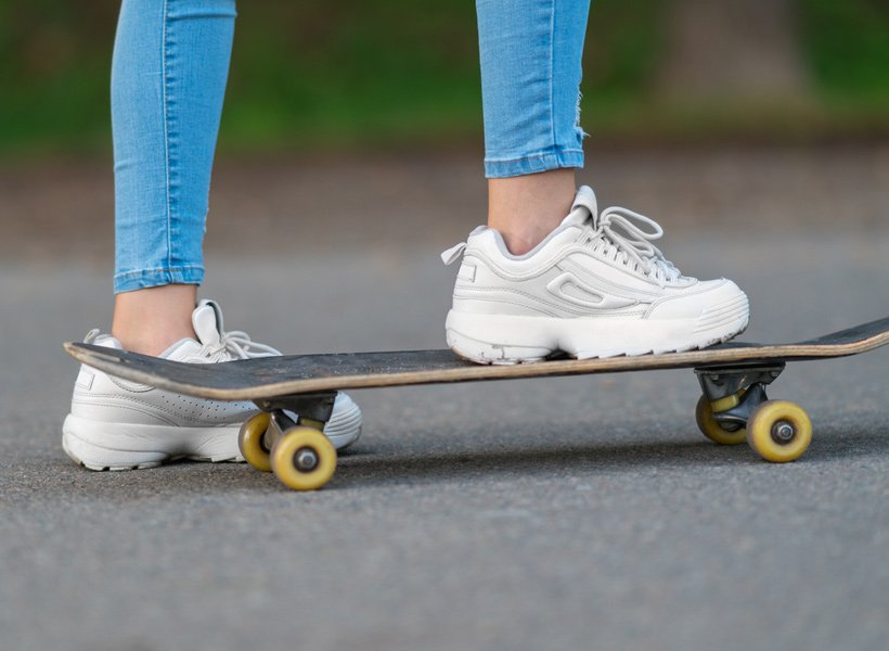 Close up shot of a girl's shoes standing on a skateboard