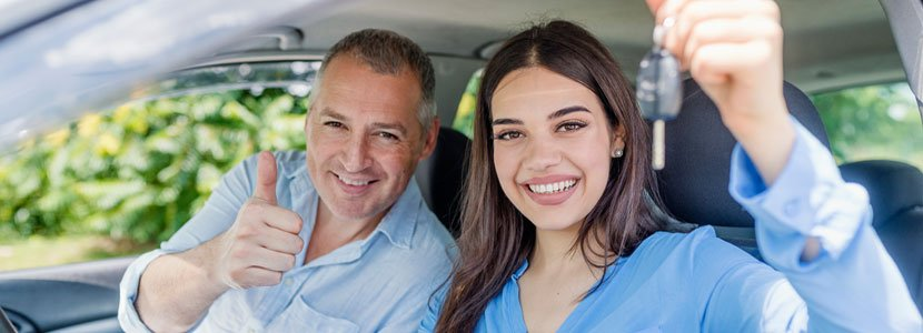 Teen driver sitting in a car next to her father