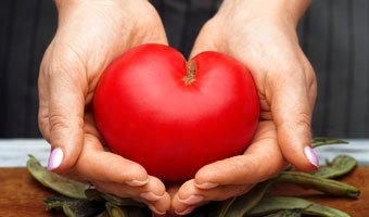Hands holding a tomato the shape of a heart