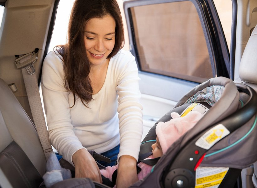 Mother placing child in a rear facing car seat