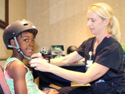 Jlyn Bradford of Buellton is properly fitted with her new safety helmet for only $10 by Registered Nurse Erin Morton