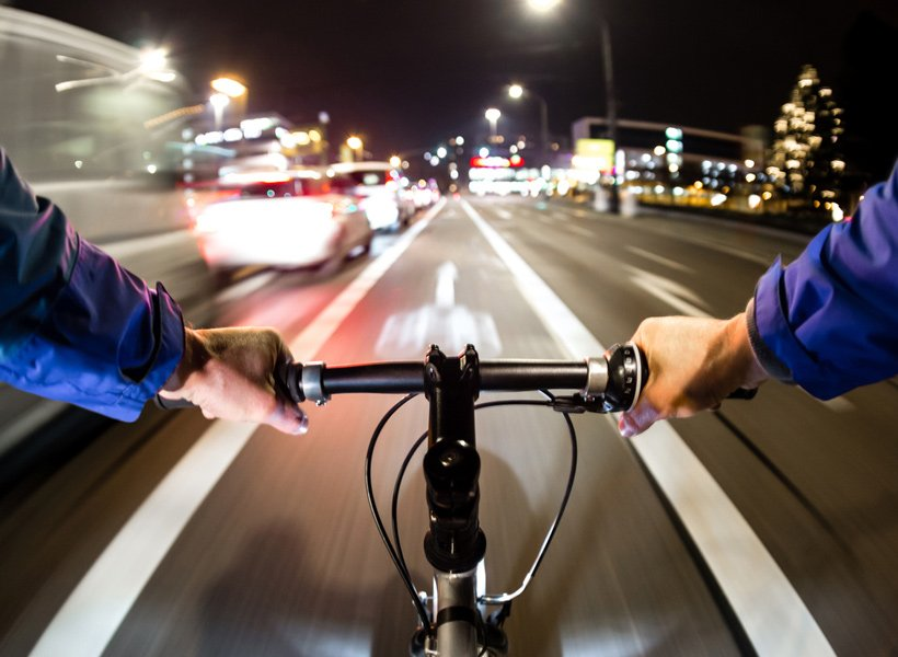 Cyclist riding on a road at night