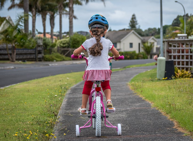 Young girl bicycling on a sidewalk next to a road