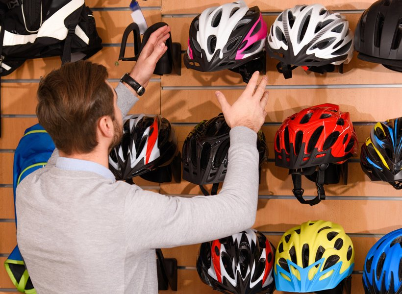 Man at a store choosing a helmet to purchase