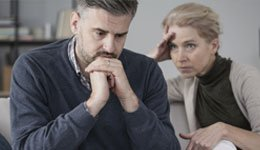 Depressed man with concerned woman sitting next to him