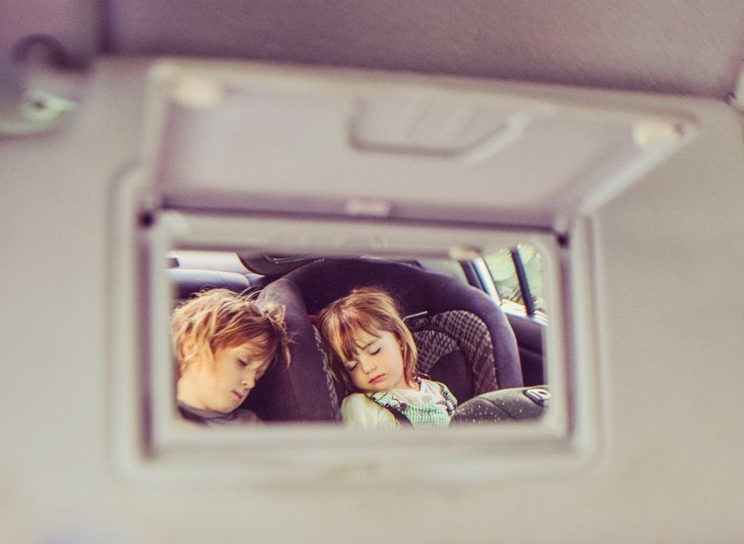 Kids sleeping in the back seat of a car