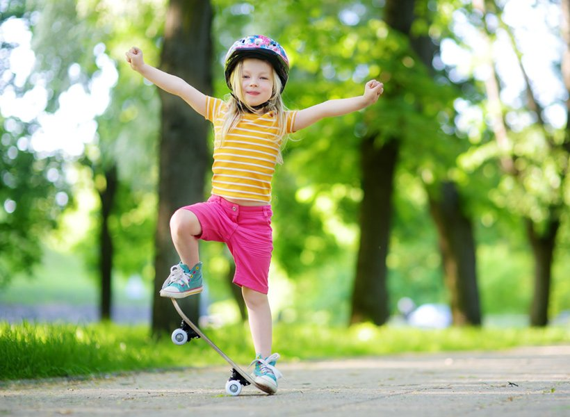 Young girl wearing a helmet standing on a skateboard with her hands raised