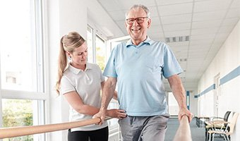 A physical therapist helping guide a patient