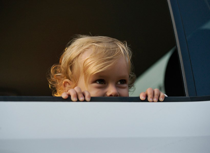 Child in back seat of a car with the window all the way down
