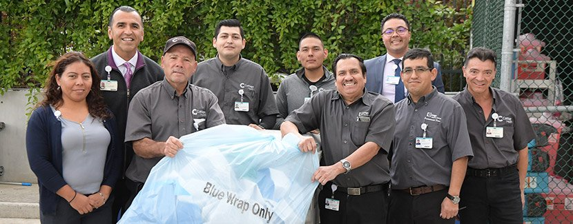 group of cottage staff holding a trash bag