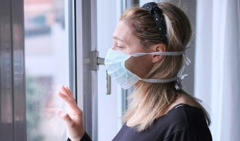 Woman wearing a face mask staring out of the window